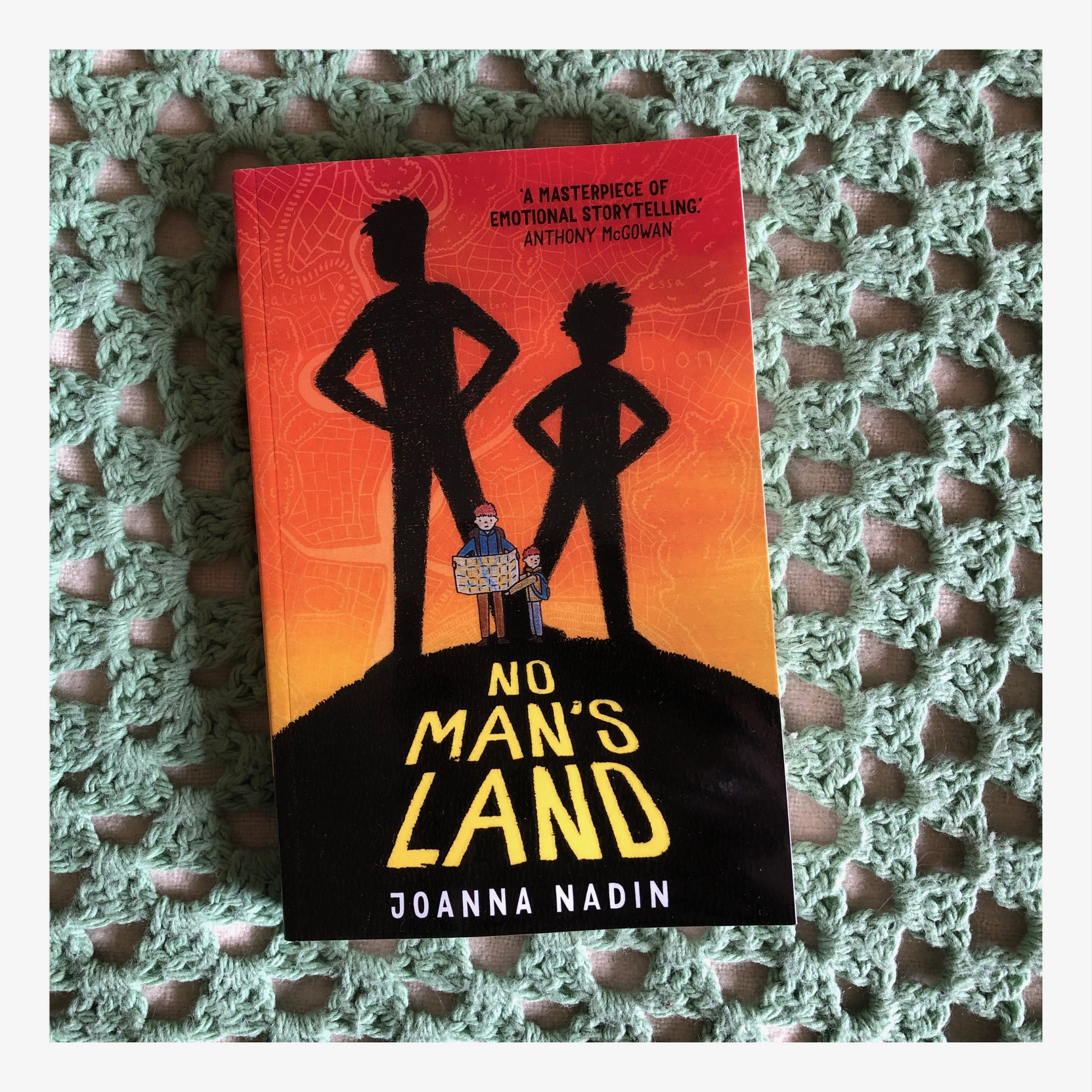 Book cover featuring two small books lost on a hill. Their shadows behind them are in superhero stance.